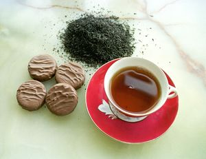 Cup of black tea with chocolate biscuits