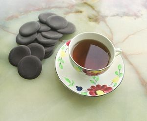 Cup of black tea with chocolate rounds